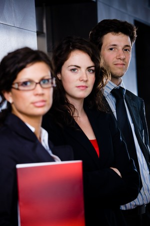 Portrait of successful happy business team posing at office lobby in front of elevator. Dark background. Stock Photo - 4083308