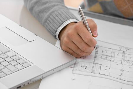 workroom: Hands of architect drawing blueprint at desk.