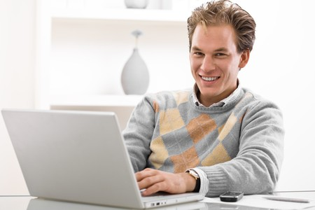 Young man working on laptop computer at home. Stock Photo - 4089947