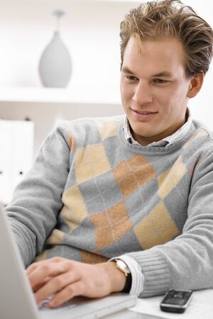 Young man working on laptop computer at home. photo