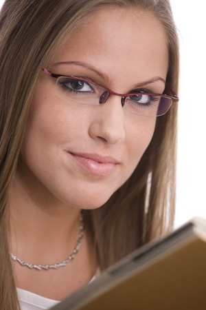 Beautiful college girl in glasses reading book. photo