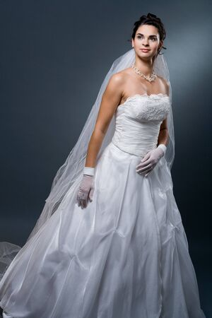 formal dress: Studio portrait of mature bride wearing elegant white wedding dress.
