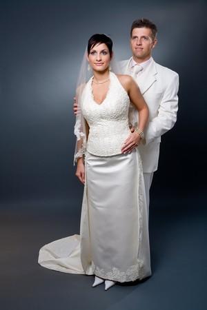Studio portrait of mid-aged couple wearing wedding dress. photo