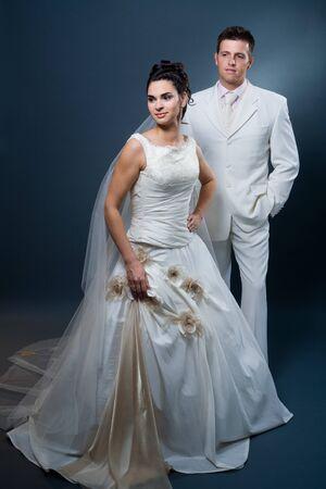 Happy bride and groom posing together in studio, wearing wedding dress, smiling.