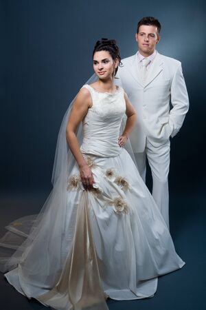 Happy bride and groom posing together in studio, wearing wedding dress, smiling. Stock Photo - 4089939