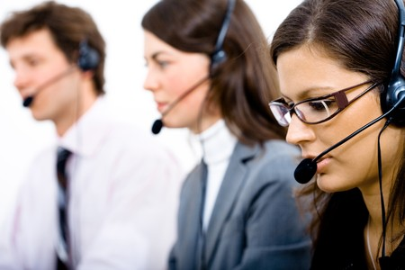 Customer service team working in headsets, woman in front. Stock Photo - 4089968