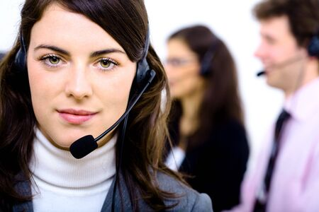 Customer service team working in headsets, smiling. Woman in front. Stock Photo - 4089987