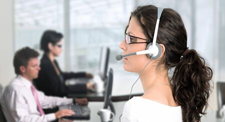 Pretty young woman works as an IT helpdesk operator. Stock Photo - 4089982