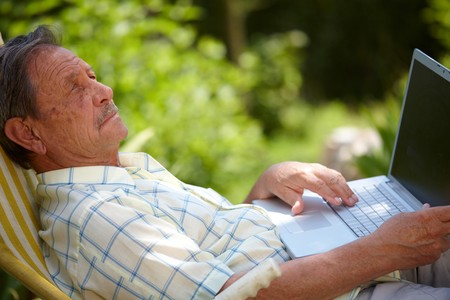 Healthy senior man is his elderly 70s sitting outdoor in garden at home and using laptop computer to browse internet. Stock Photo - 4090353