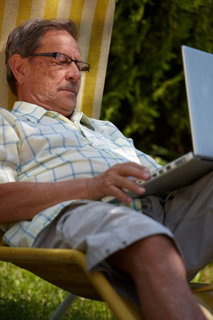 Healthy senior man is his elderly 70s sitting outdoor in garden at home and using laptop computer to browse internet. Stock Photo - 4090354