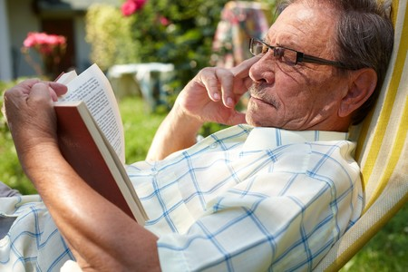 Healthy looking old man is his late 70s sitting in garden at home and reading book, outdoor. photo