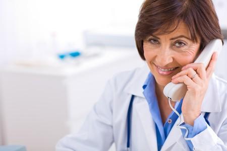 Senior female doctor calling on phone, smiling. Stock Photo - 4089978