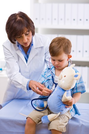 Senior female doctor examining little child boy. photo