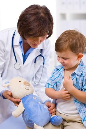 doctora: Superior de las mujeres m�dico y el examen de ni�o feliz osito de peluche.