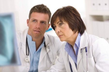 Doctors coworking looking at x-ray image at office. Stock Photo - 4089986