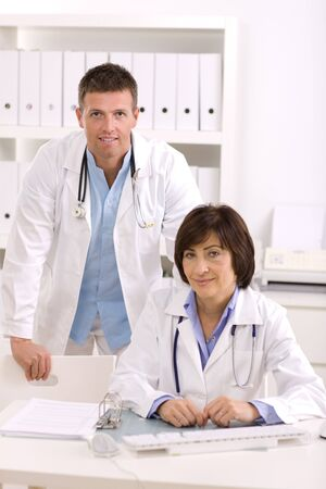 Medical doctors working in team at office, smiling. Focus on male. photo