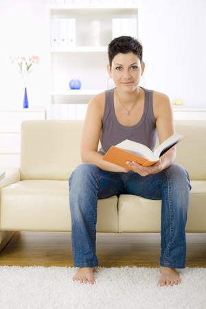 Young woman reading book at home, sitting on sofa. photo