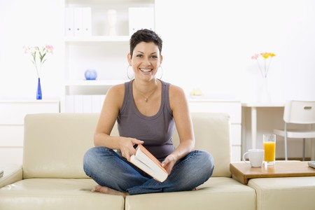 Female student sitting on sofa at home, reading book. Stock Photo - 4087757