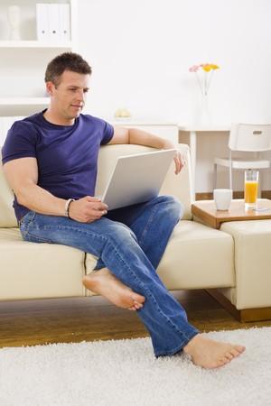 outwork: El hombre que navega en Internet ordenador port�til en casa. Foto de archivo