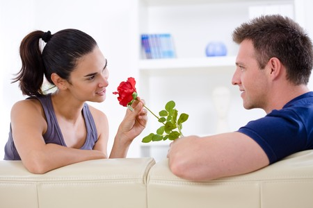 man couch: Romantic man giving red rose to woman - Valentines Day. Stock Photo