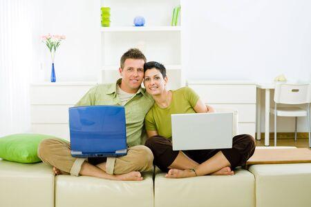 outwork: Amor joven trabajando juntos en ordenador port�til en casa.