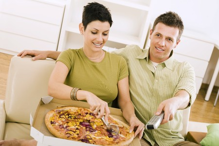 Couple eating pizza and watching TV at home. photo