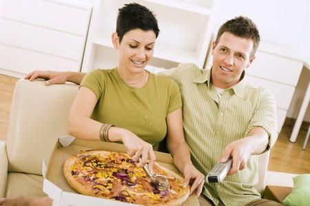 pareja comiendo: Joven comiendo pizza y viendo televisi�n en casa.