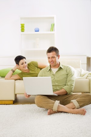 outworking: Couple browsing internet on laptop on laptop computer at home. Stock Photo