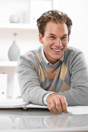 workroom: Happy young man working at desk at home. Stock Photo