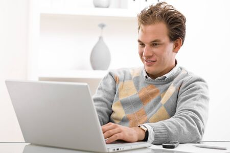 Young man working on laptop computer at home. Stock Photo - 4087766