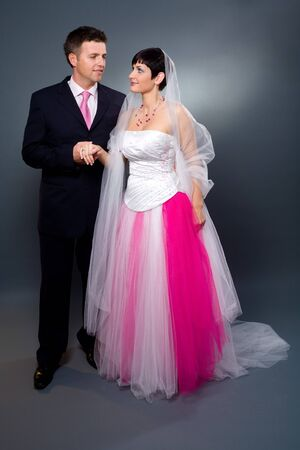 Bride and groom in studio wearing pink and white wedding dress. photo