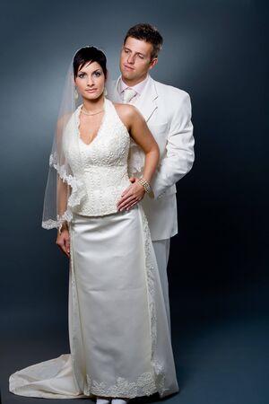 Loving bride and groom posing together in studio wearing wedding dress. Stock Photo - 4087748