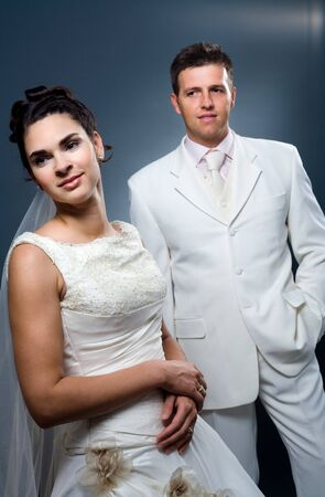 Happy bride and groom posing together in studio, wearing wedding dress, smiling. photo