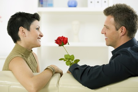 Romantic man giving red rose to woman at home, smiling. Stock Photo - 4087770