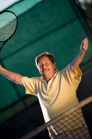70s tennis: Active senior man in his 70s is posing on the tennis court with tennis racket in hand. Outdoor, sunlight.