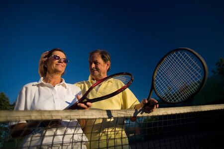 Active senior couple is posing on the tennis court with tennis racket in hand. Outdoor, sunlight. photo