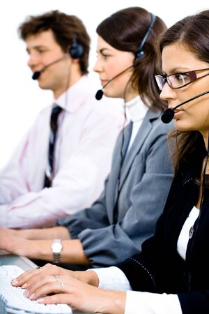 telework: Customer service team working in headsets, woman in front.