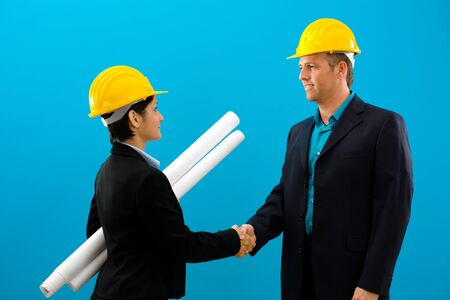 Arhitects shaking hands isolated on blue background. Stock Photo - 4100523