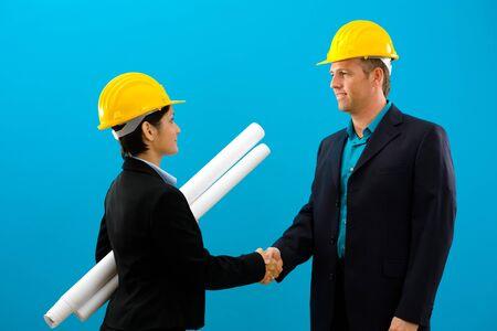Arhitects shaking hands isolated on blue background. Stock Photo - 4100523