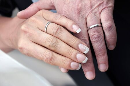 weddingrings: Hands of an aged couple who still wear their wedding-rings as the sign of their togetherness.