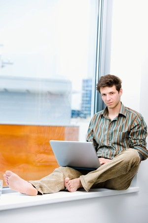 sinecure: Young casual office worker sitting at office window working on laptop computer.