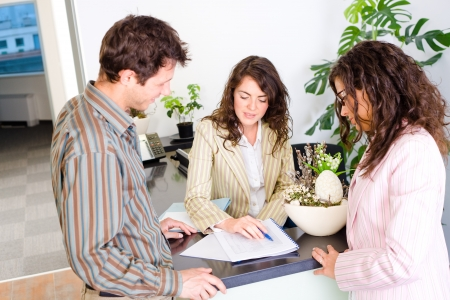 Casual business team working together at office reception, looking at documents, talking. photo