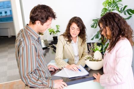 ropa casual: Casual de negocios trabajando juntos en equipo de oficina de recepci�n, ver documentos, hablar. Foto de archivo