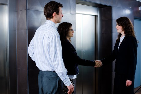 Smiling business people shaking hands at office lobby in front of elevator. Stock Photo - 4107035