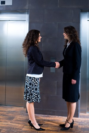 businesswear: Smiling business people shaking hands at office lobby in front of elevator. Stock Photo