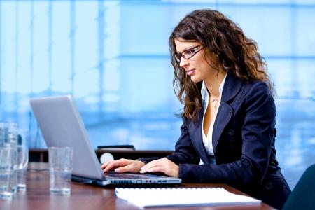 secretaries: Feliz joven empresaria de trabajo en ordenador port�til en la oficina, sonriendo. Foto de archivo