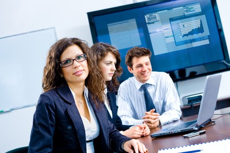colleague: Small team of young businesspeople working together at meeting room at office. Huge plasma TV screen in background. Stock Photo