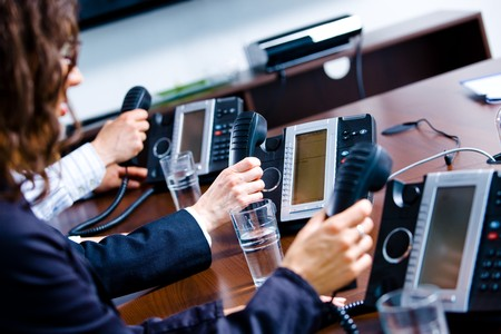 dispatcher: Close-up of hands holding landline phone recievers at customer service office.