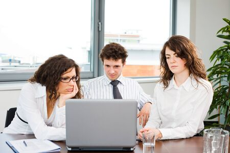 Young business people working together on laptop computer in meeting room at office.