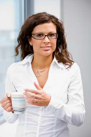 Young businesswoman standing in front of office window, drinking coffee and thinking. photo
